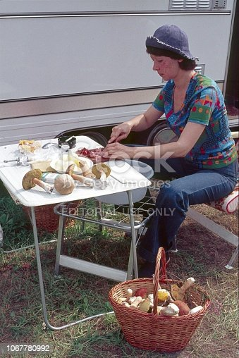Ebeltoft, Denmark, 1976. A woman (vacationer) prepares a meal beside his camper. On the table and in a basket on the ground are self-collected mushrooms.