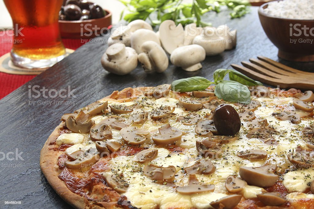 Mushroom pizza with a glass of beer and ingredients royalty-free stock photo