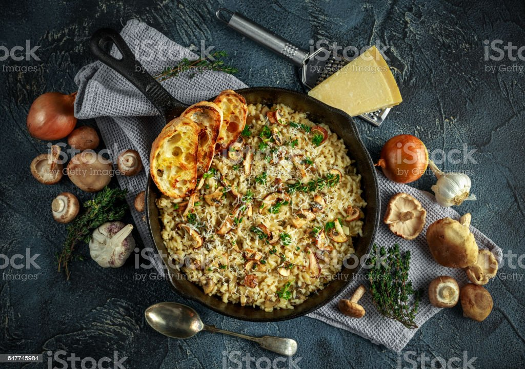 Mushroom Risotto in iron pan with herbs and parmesan cheese stock photo
