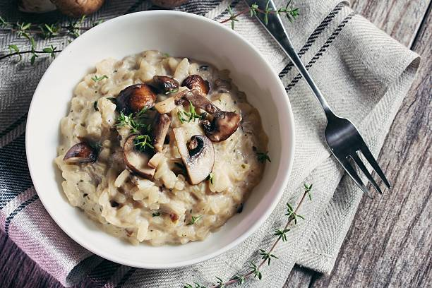mushroom risotto served in a bowl, selective focus - food styling stock photos and pictures