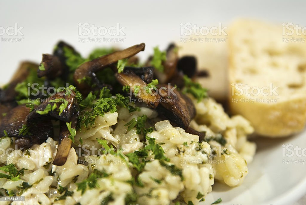 Mushroom risotto with chopped herbs and sliced bread stock photo