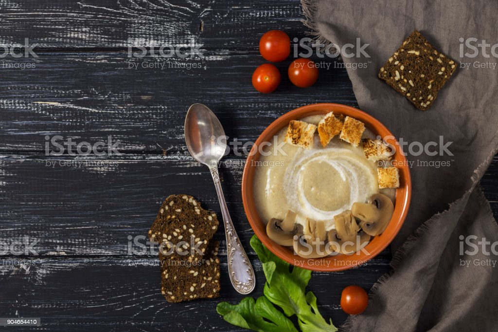 Mushroom soup puree. A cup of mushroom soup with rusks on a rustic background with a napkin and a spoon. stock photo
