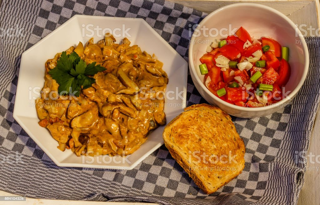 Mushroom stew with parsley, tomato salad, and bread royalty-free stock photo