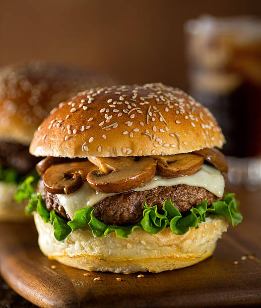 Mushroom Swiss Burger A delicious gourmet hamburger topped with swiss cheese and fried mushrooms on a rosemary sesame seed bun. swiss culture stock pictures, royalty-free photos & images