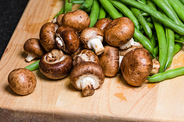 Mushrooms and green beans on a wooden board stock photo