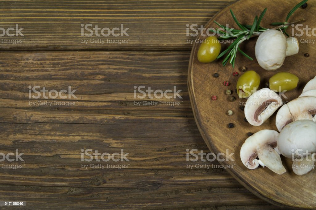 Mushrooms and olives on a wooden board stock photo