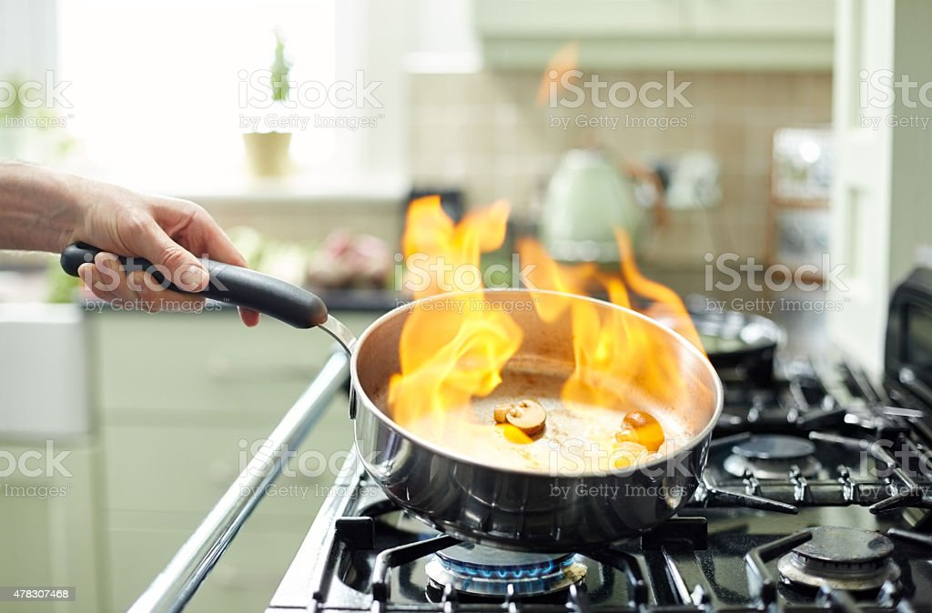 Mushrooms being prepared in pan with flames stock photo