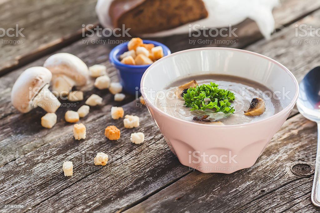Mushrooms cream soup and crackers on a wooden background stock photo