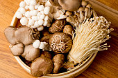 Assortment of mushrooms, portobello, chanterelles, hen of the woods, shiitake and button mushrooms shot in wooden basket on wooden cutting board.