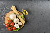 istock Mushrooms mushrooms, lettuce, tomatoes and spaghetti on stone table. Top view. 931933910