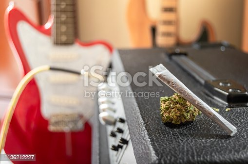 istock Music and marijuana, looking inspiration. Weed joint and big marijuana bud on guitar speaker. Musical instruments in the background with blur effect. 1136212227