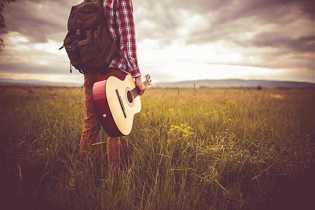 Music and nauture Photo of young man in nature with guitar folk music stock pictures, royalty-free photos & images