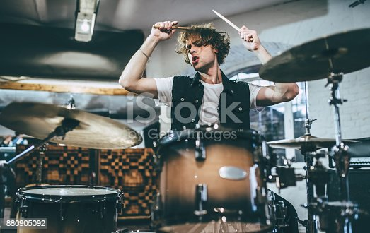 Repetition of rock music band. Drummer behind the drum set. Rehearsal base