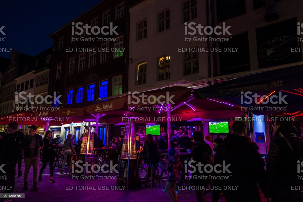 People enjoy music bars and restaurants at night in Altstadt of...