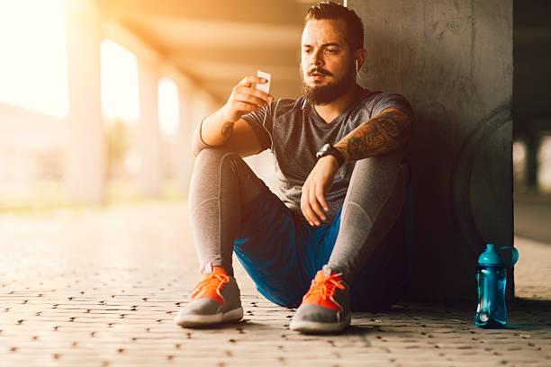 musik pause nach joggen. - laufende tattoos stock-fotos und bilder