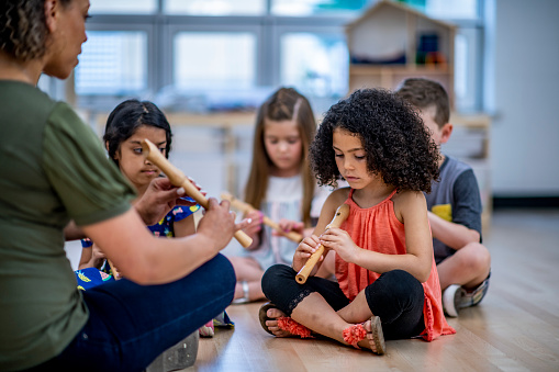 A female teacher of african descent plays the recorder with her class. They are all focused on their finger placements on the instrument.