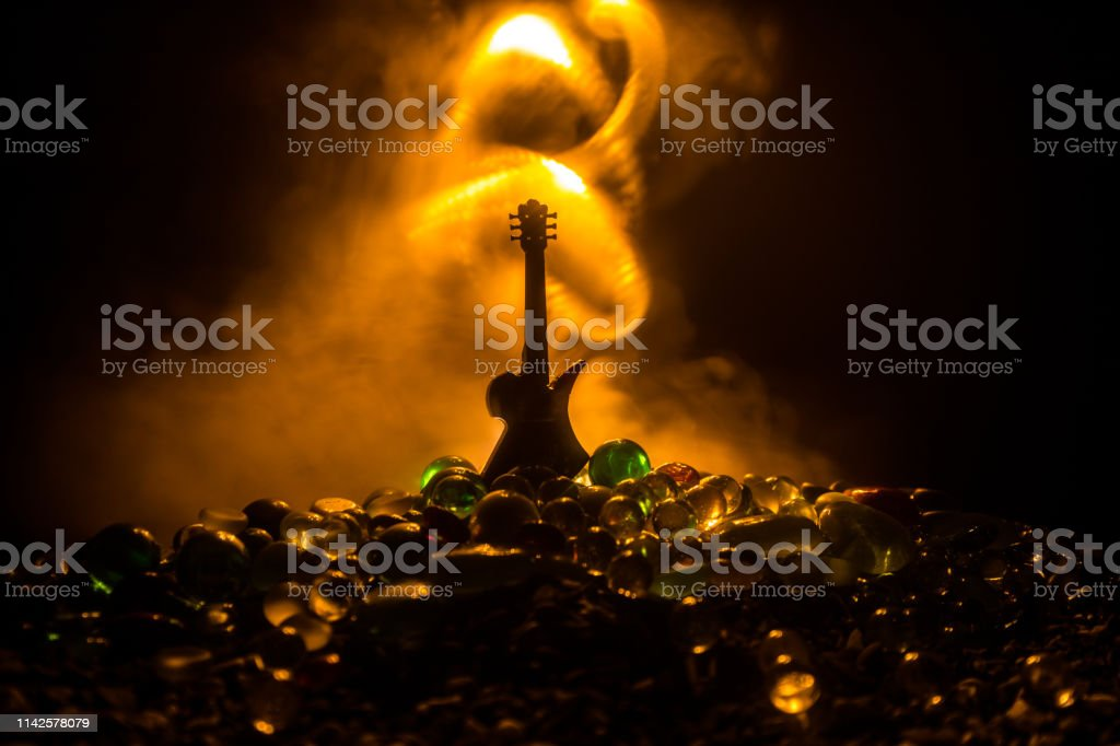 Music concept. Acoustic guitar on a dark background under beam of...