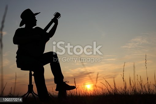 Music concept of black silhouette of man with western hat (cowboy) and instrument with grass at sunset or sunrise. Musician play guitar in summer night. Theme of relax, balance, calm with copy space.