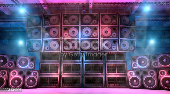 Loudspeakers and subwoofers stacked on each other on a music concert stage illuminated by blue and magenta lights, with foggy and smokey atmosphere. Punk and hard rock music background. Powerful sound system. Digitally generated image.