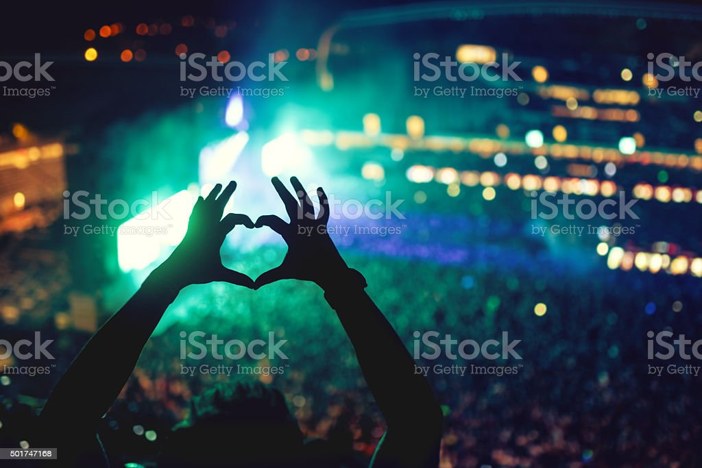 Music concert with lights and silhouette of man enjoying concert stock photo