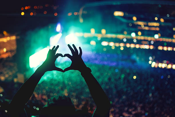Music concert with lights and silhouette of man enjoying concert Heart shaped hands at concert, loving the artist and the festival. Music concert with lights and silhouette of a man enjoying the concert fan club stock pictures, royalty-free photos & images