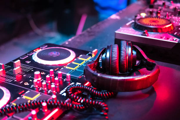 DJ music console in bright colors of light in night club DJ music console in bright colors of light in night club bright background dj stock pictures, royalty-free photos & images