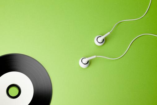 Photograph of earbuds wriggling towards a compact disc. Abstract representation of sperm cells fertilising an ovum.
