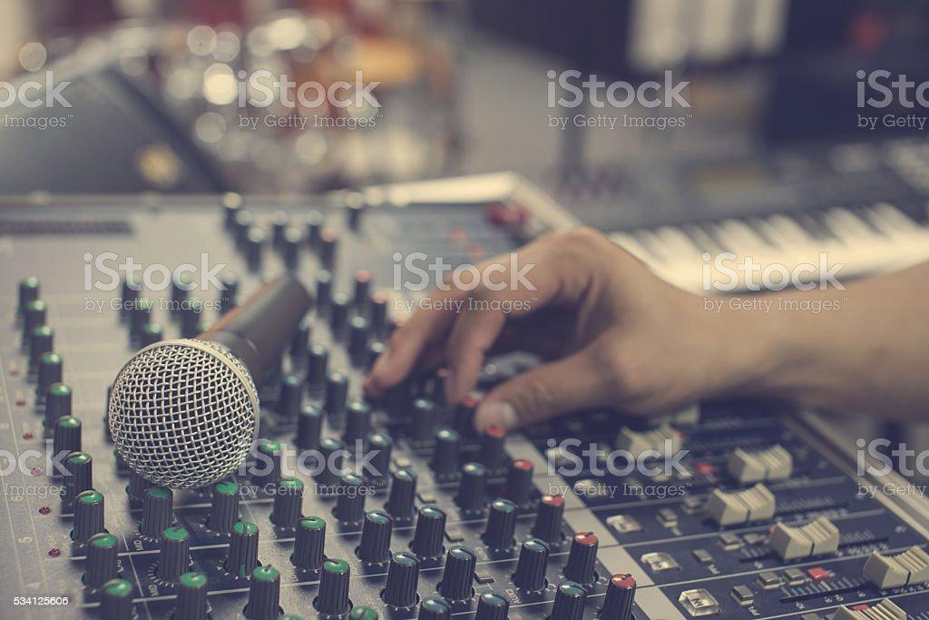 music equipment mic and blur hand adjust audio mixer stock photo