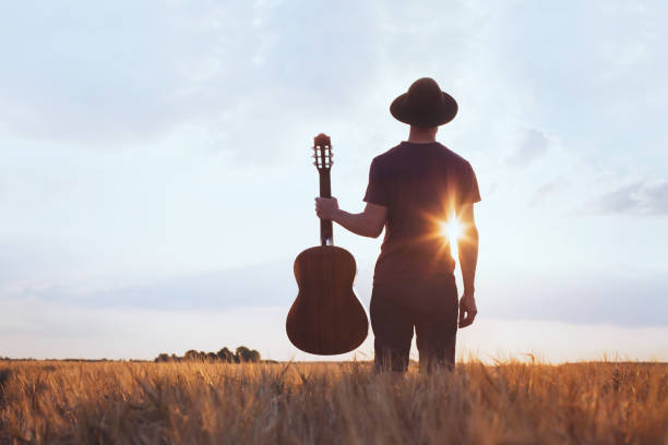 music festival background, silhouette of musician artist with acoustic guitar music festival background, silhouette of musician artist with acoustic guitar at sunset field country and western music stock pictures, royalty-free photos & images