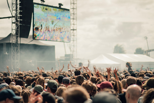 A crowd have fun at a music festival.