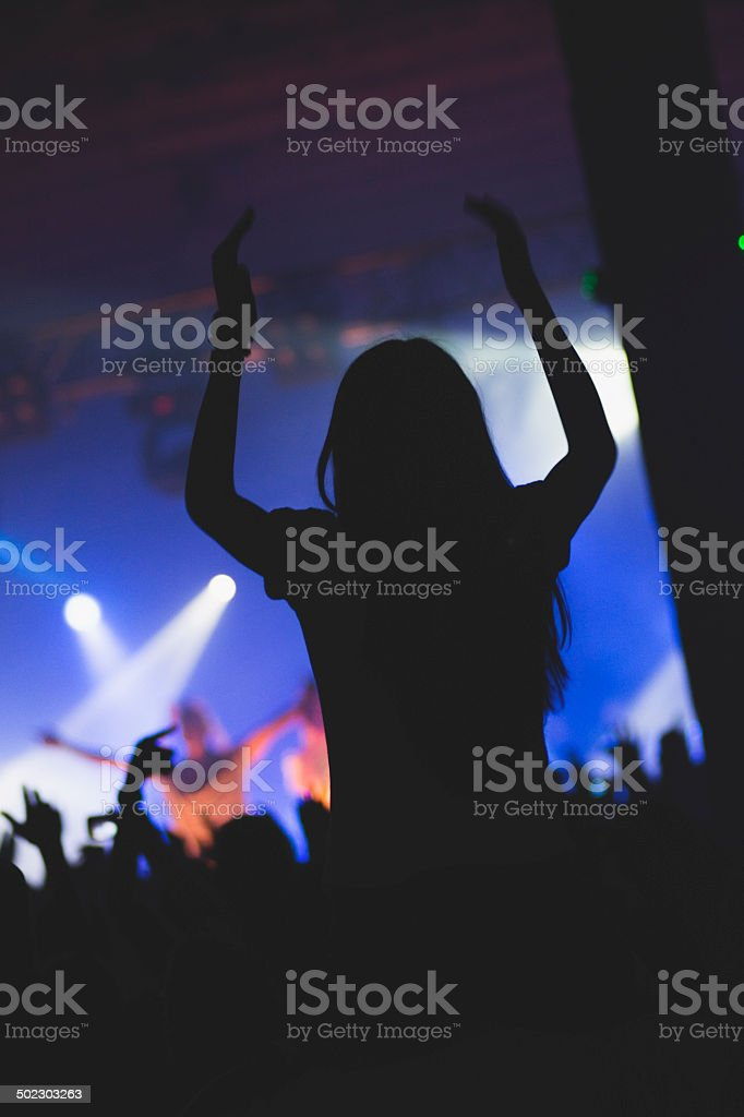 Girl at the concert, hands in the air.