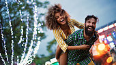 Young couple enjoying at music festival. They are laughing and looking at camera.