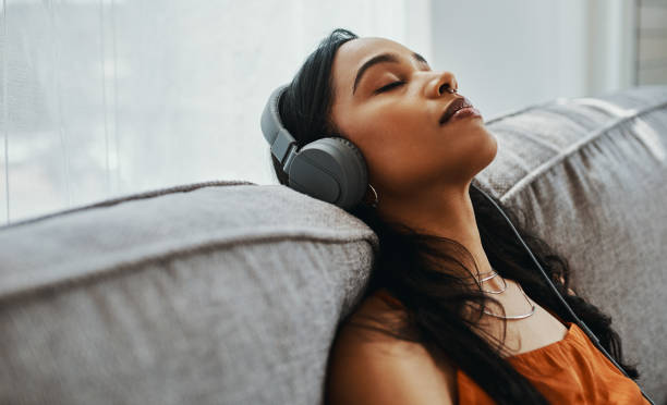 Music first, life later Shot of a young woman using headphones while relaxing on the sofa at home relaxation stock pictures, royalty-free photos & images