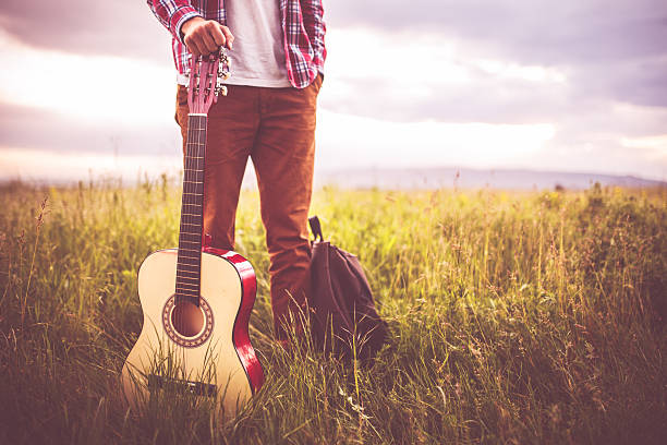 Music in nature Photo of young man in nature with guitar folk music stock pictures, royalty-free photos & images