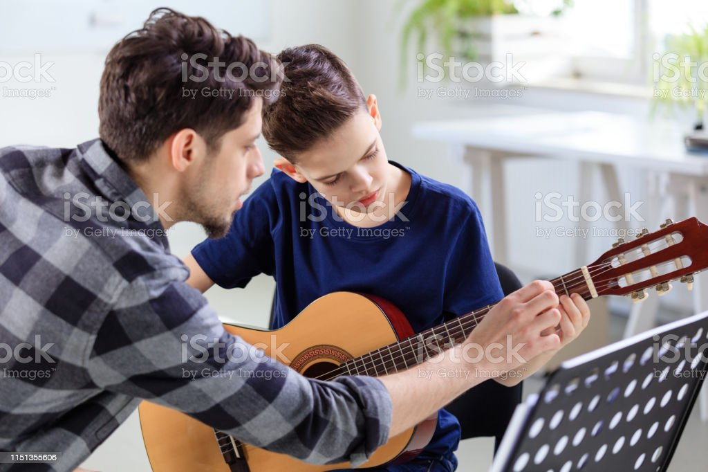 Music instructor explaining guitar strings to boy Music instructor explaining guitar strings to boy in classroom. Pre-adolescent guitarist is learning musical string instrument in training class. They are at conservatory. 12-13 Years Stock Photo