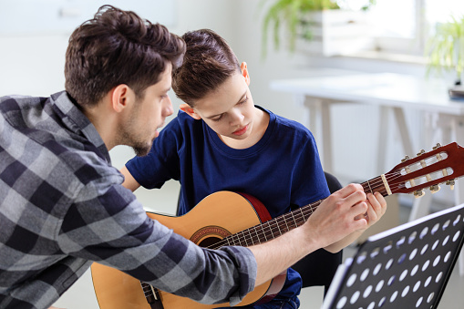 Music Instructor Explaining Guitar Strings To Boy Stock Photo - Download Image Now