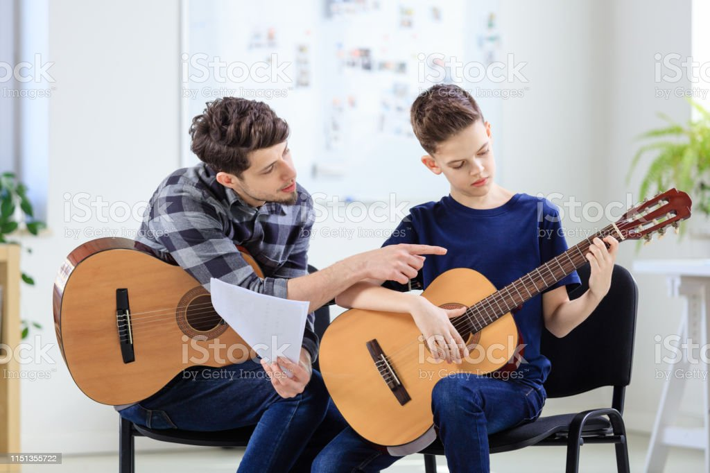 Music instructor explaining guitar to boy in class Music instructor explaining guitar to boy in classroom. Pre-adolescent guitarist is learning string instrument in training class. They are at conservatory. 12-13 Years Stock Photo