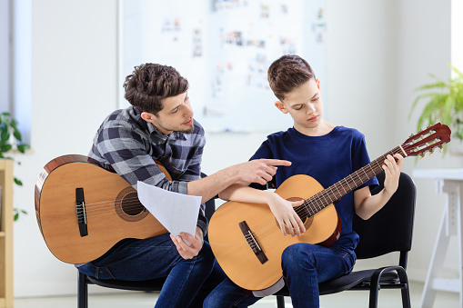 Music Instructor Explaining Guitar To Boy In Class Stock Photo - Download Image Now