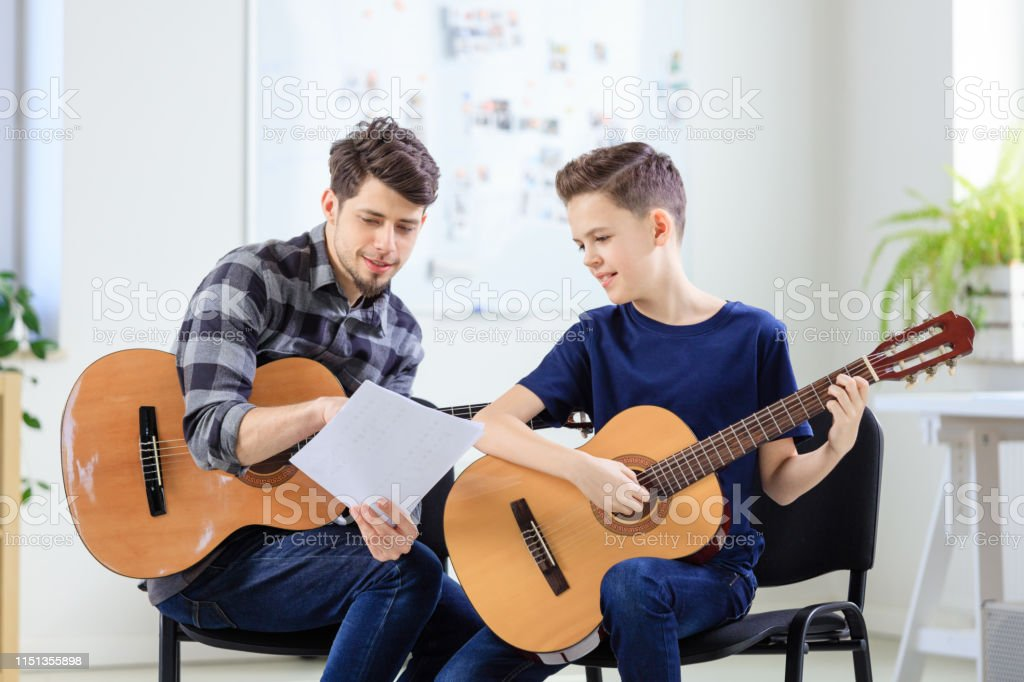 Music instructor explaining sheet to boy in class Music instructor explaining sheet to boy in training class. Pre-adolescent guitarist is learning string instrument. They are in classroom at conservatory. 12-13 Years Stock Photo
