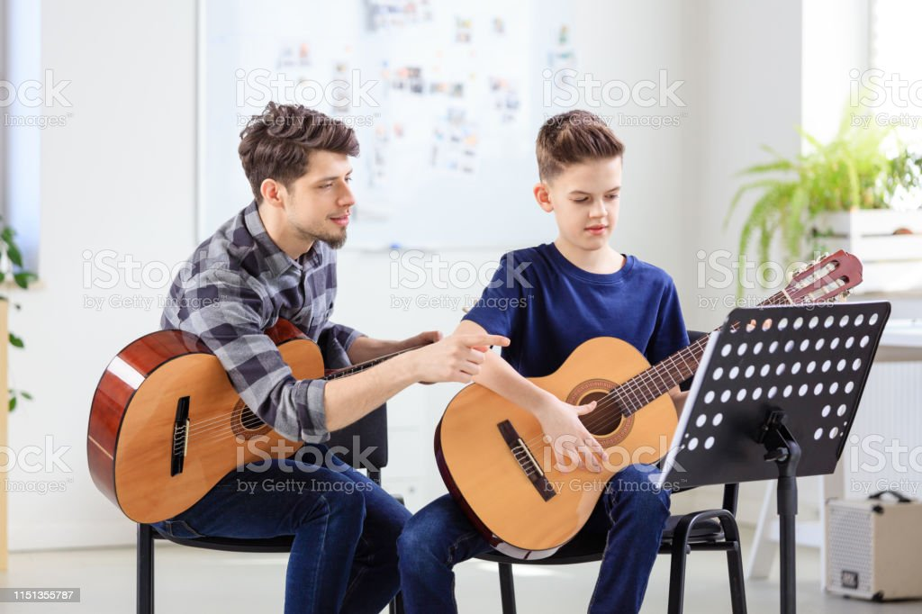 Music instructor explaining sheet to boy Boy and instructor practicing guitar in training class. Pre-adolescent guitarist is training with teacher in classroom. They are at conservatory. 12-13 Years Stock Photo