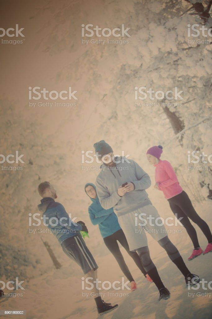 Attractive sportsman is standing on snowy mountain and looking at...
