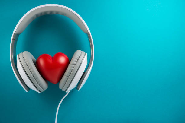 Music is my life, headphones and red heart on blue background stock photo