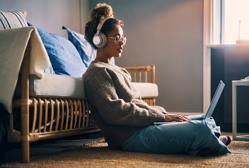 Shot of a young woman wearing headphones while using a laptop at home