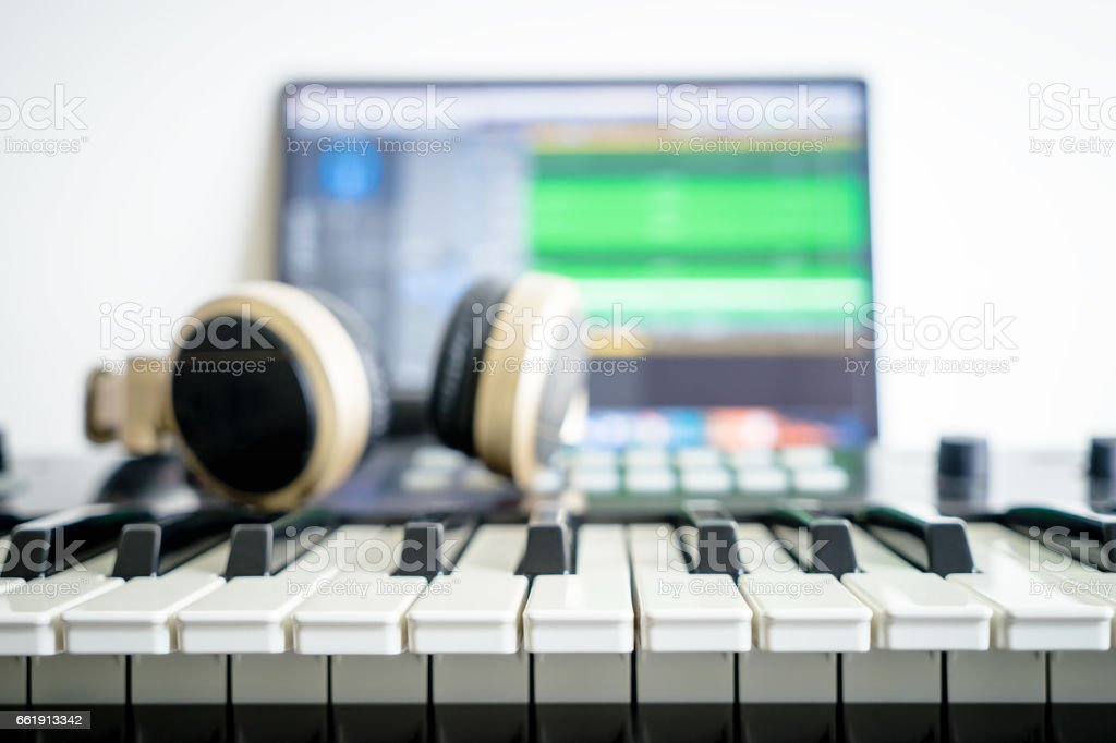 Music keyboard and Music mixing headphone on computer music station stock photo