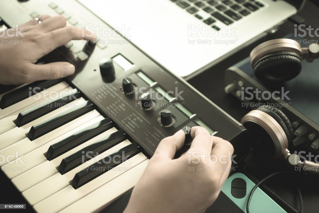 Music keyboard player is adjusting sound on synthesizer stock photo