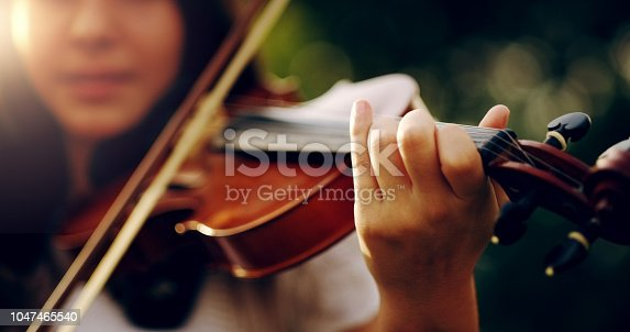 Cropped shot of an unrecognizable teenage girl playing a violin outside