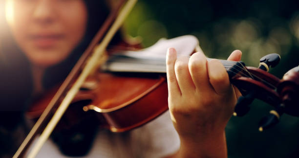 Music lifts the spirit and enlightens the soul Cropped shot of an unrecognizable teenage girl playing a violin outside string instrument stock pictures, royalty-free photos & images