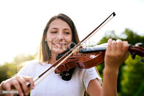 Shot of a cheerful young girl playing the violin while standing in the backyard of her home during the day