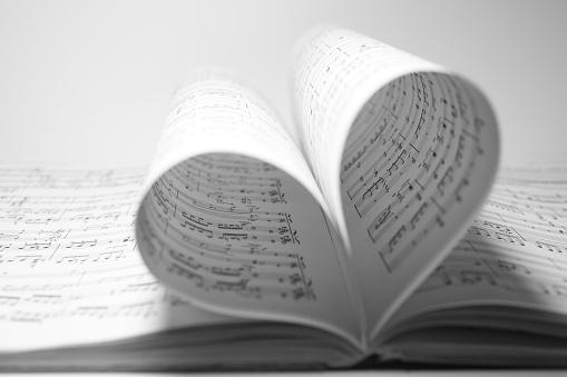 Sheet music bending into a heart shape.