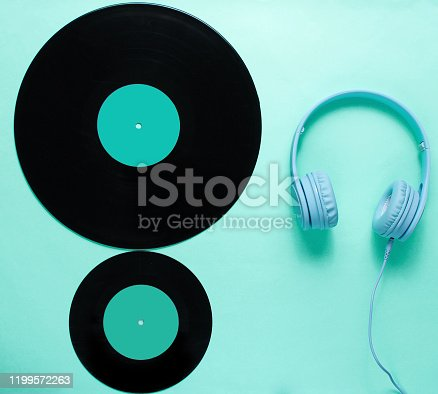 Music lover. Headphones, lp records on blue background. Retro culture. Flat lay. Top view
